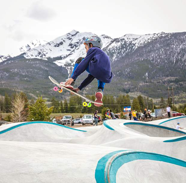A young skater grabs his board while riding through the new, expanded and re-imagined Frisco Skatepark on June 4, the twin peaks of Peak One and Tenmile Peak in view in the distance.