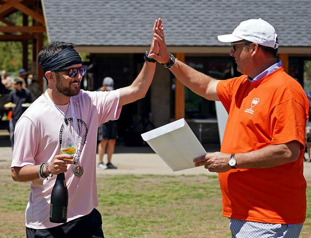 The overall top finisher for males in Robbie's Run 5K, Kyle Brochu, high-fives Breckenridge Grand Vacations CEO and president Mike Dudick during the fourth annual Rob Millisor Heart Health Walk on June 8 at Carter Park in Breckenridge.