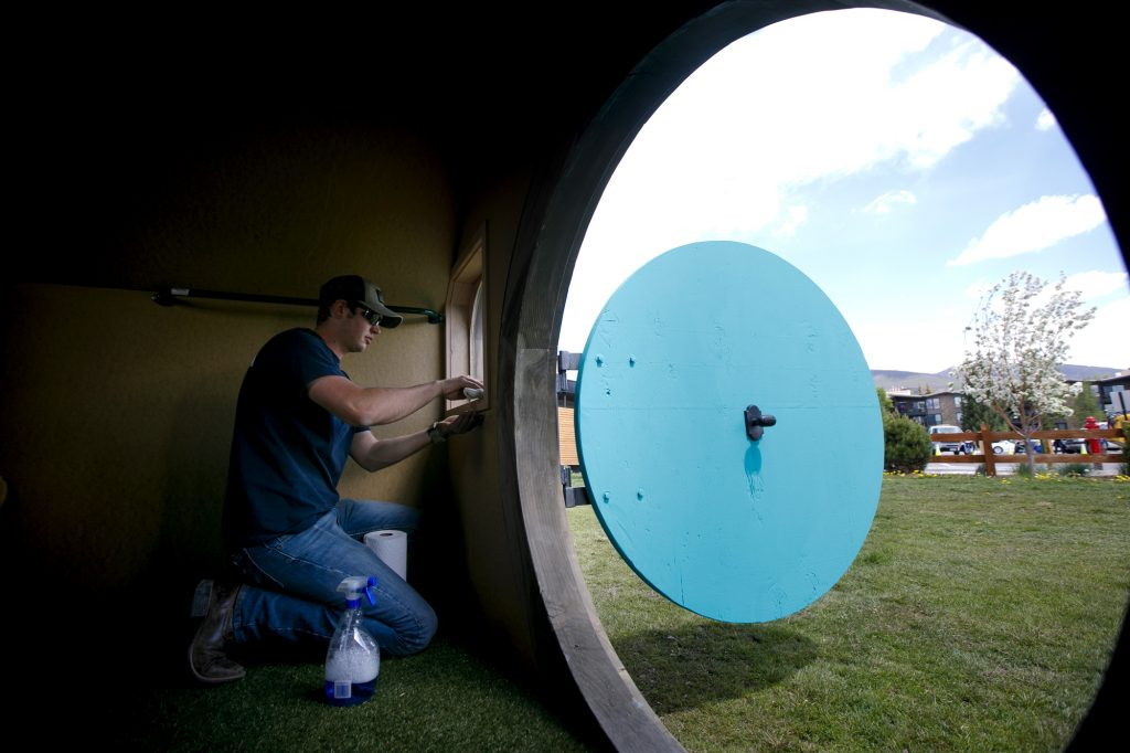 Marcus Sandberg, of Campbell Construction, makes final touches inside a playhouse Thursday, June 27, in Dillon.