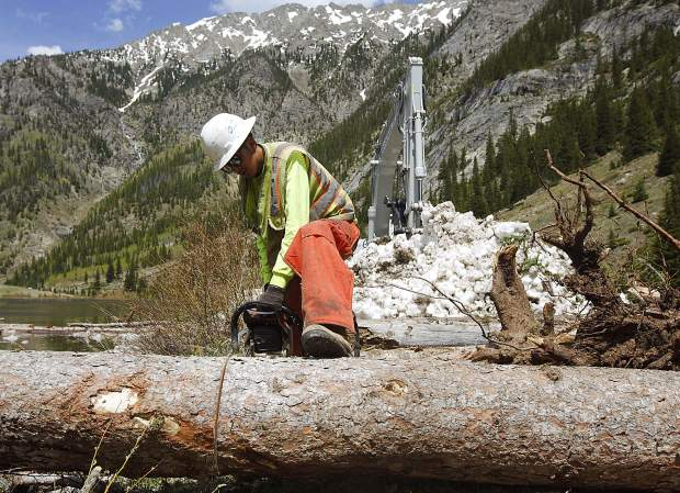 Martin Mata, of RPM Construction, uses the chainsaw to clear avalanche debris off the recreational pathway Thursday June 13, near Copper Mountain.