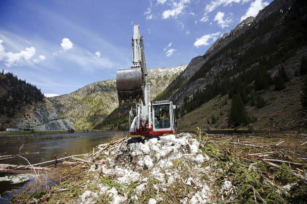 Roby Forsyth, of RPM Construction, operates the heavy machinery to clear avalanche debris off the recreational pathway for the Summit County Thursday June 13, near Copper Mountain.
