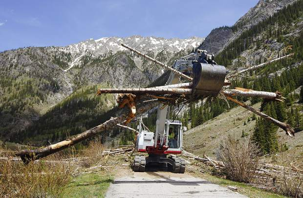 Crews for Summit County work to clear avalanche debris off the recreational pathway in Tenmile Canyon on June 13 near Copper Mountain.
