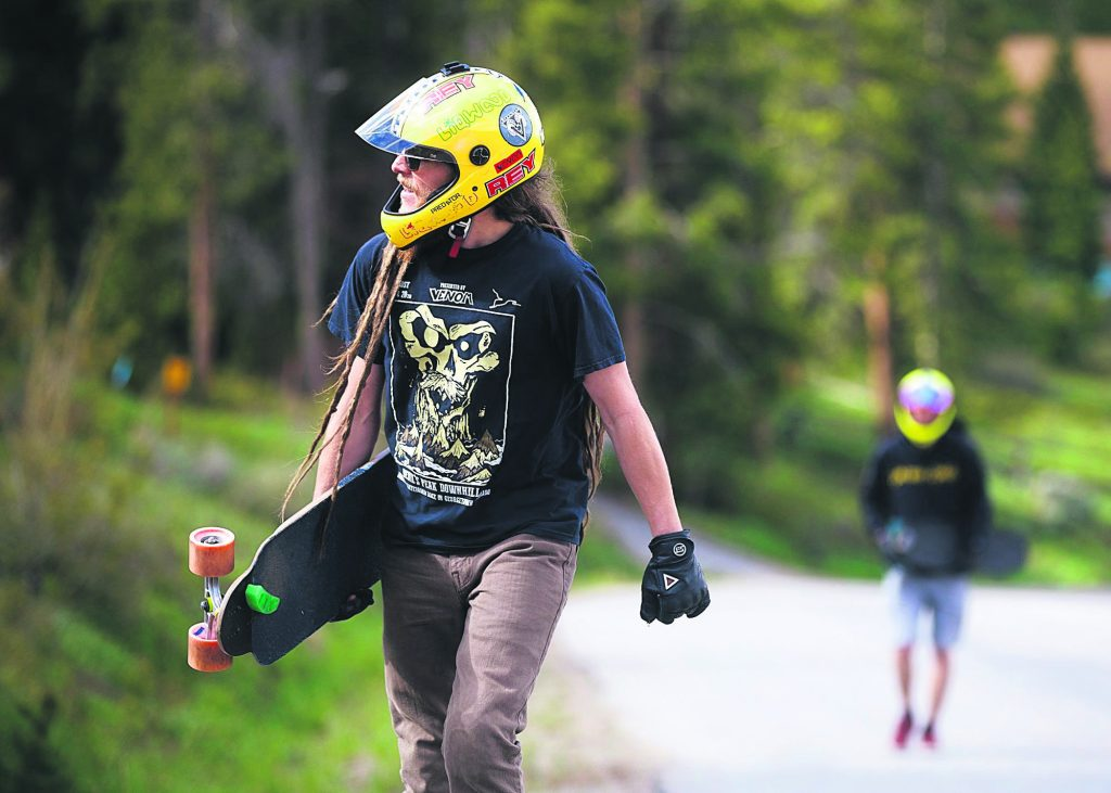 Kyle Peel walks back up the road with his skateboard in hand, his green foot-stop in view at the front of the board, for another downhill skateboarding lap on Friday June 21, in Breckenridge.