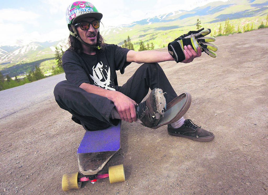 Frisco born-and-raised local Mike DeGrado examines his worn shoes used for breaking during downhill luging on a skateboard on Friday June 21, in Breckenridge.