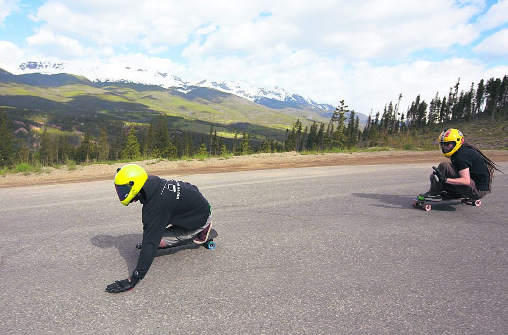 Russell Janoviak, left, and Kyle Peel shift some of their balance to their palms to control speed into a turn while downhill skateboarding on Friday June 21, in Breckenridge.