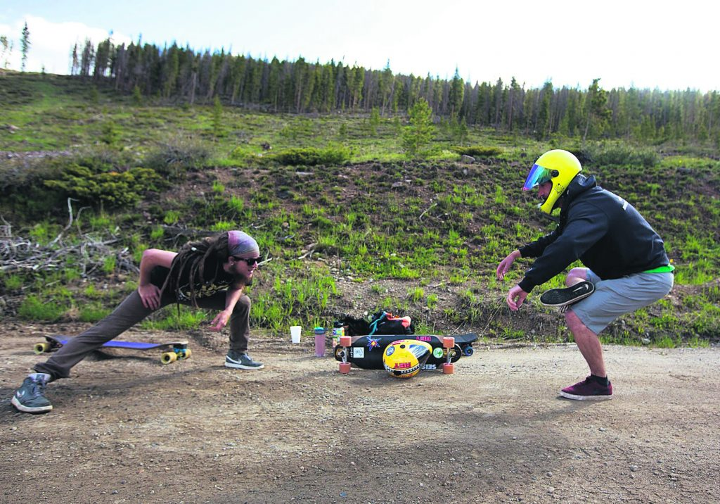 Russell Janoviak, right, and Kyle Peel stretch before downhill skateboarding on Friday June 21, in Breckenridge.