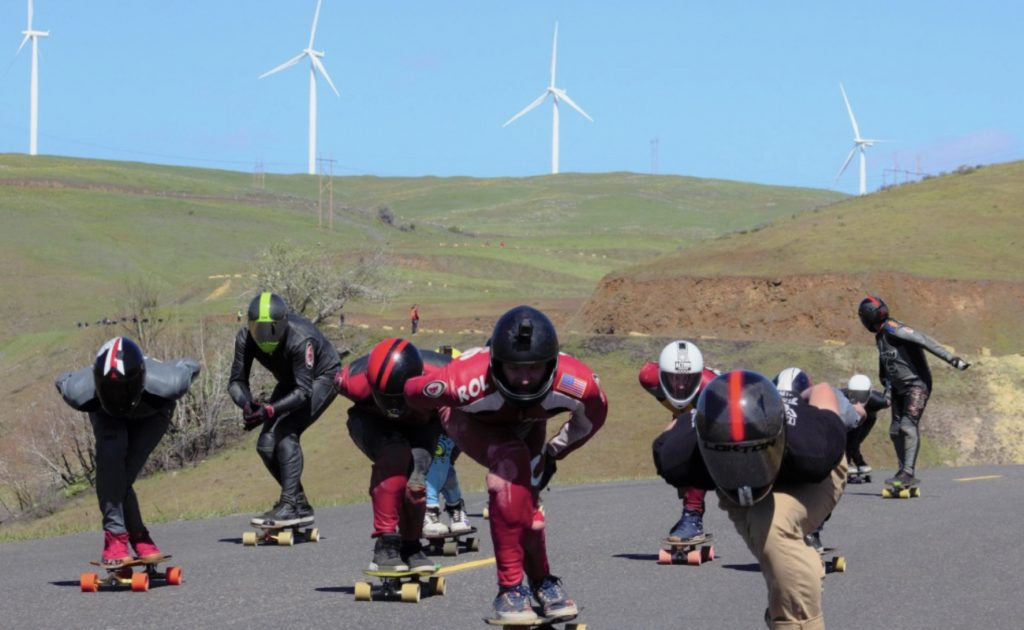 The crew of downhill skateboarders tuck to gain speed while riding all together at the Maryhill Festival of Speed in Washington state.