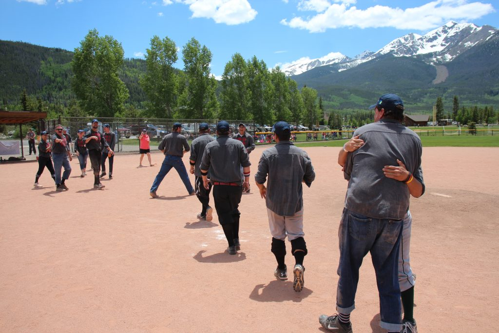 The Summit Sluggers hug in the inner garden to celebrate their 19-12 victory over the visiting Star Base Ball Club of the Colorado Territory on Saturday at the Frisco Adventure Park, the snow-capped TenMile Range in view in the distance.