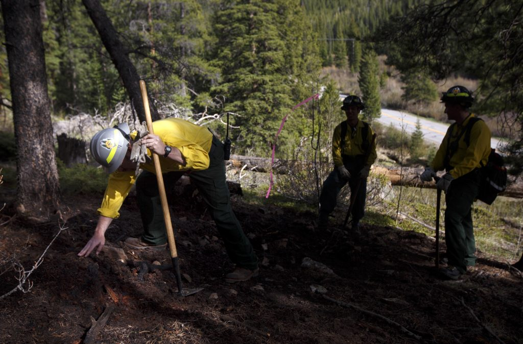 Summit Fire and EMS firefighter Dennis Jackson, left, investigates a burn area from a small ground fire Tuesday, June 11, near Montezuma.