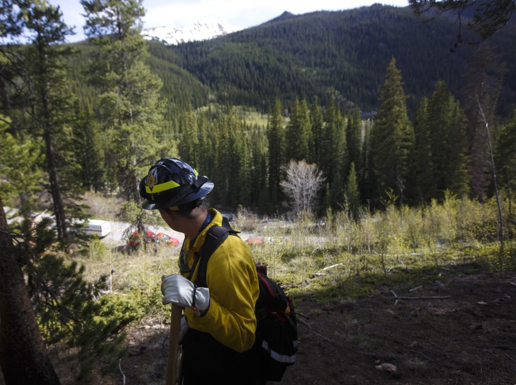 A Summit Fire and EMS firefighter looks across the valley after containing a small ground fire Tuesday, June 11, near Montezuma.