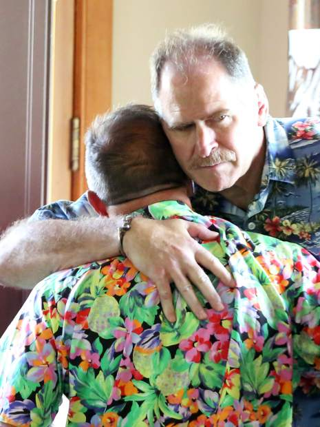 Bo Buck, back, hugs Gary Williams during the memorial for Jerome Hatem last Monday, June 17 at Mountain Chalet in Aspen.