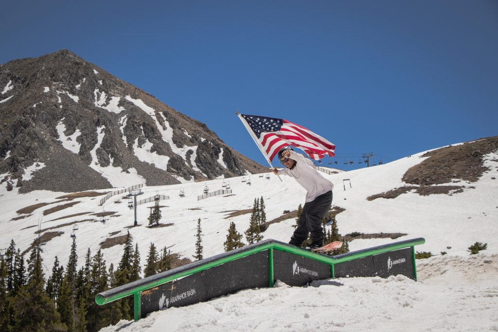A snowboarder holds Old Glory high while riding a rail at Arapahoe Basin Ski Area in honor of Independence Day.