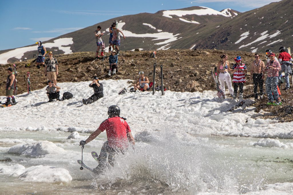 A skier skims across the Lake Reveal pond skim at Arapahoe Basin Ski Area on Thursday, July 4.