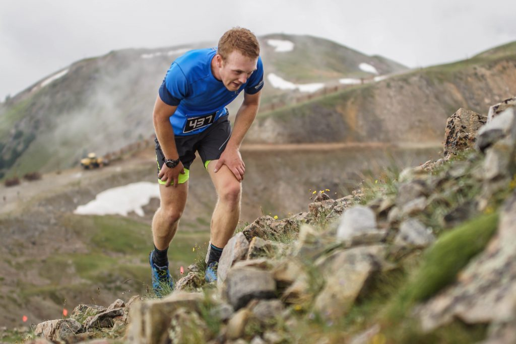 A mountain runner powers through some of the final steps up to the top of Little Lenawee Peak in the high-Alpine of Arapahoe Basin Ski Area during the August 2018 Cirque Series mountain running event.