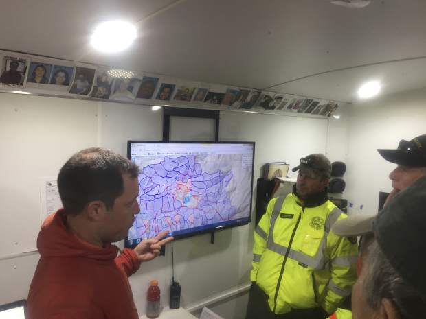 This April 17, 2017, photo provided by Michael St. John shows search and rescue volunteer and SARTopo creator Matt Jacobs, left, and search and rescue volunteers Mike Russo, center, and Bob Gehlen, right, in Sierraville, California, as they consult a SARTopo map while making plans to search for a missing aircraft.