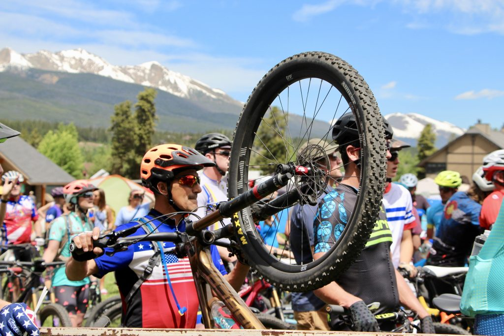 A mountain biker taking part in the Firecracker 50 holds his front wheel in the air.