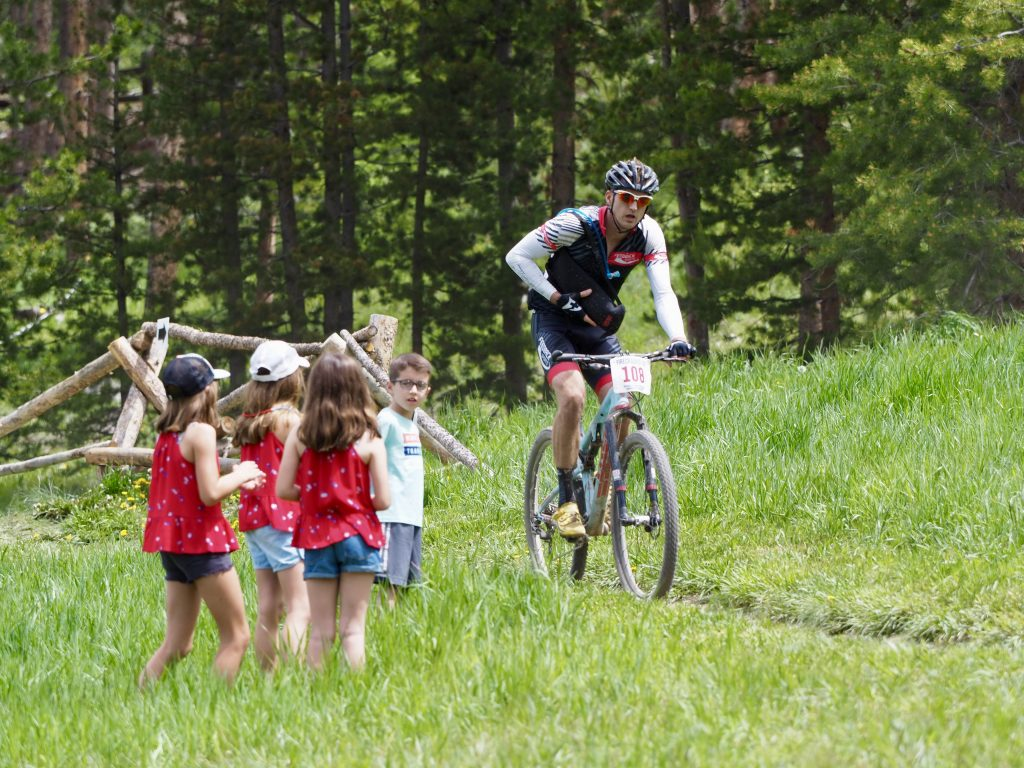 Kids watch as Ross Delaplane pedals during Thursday's Firecracker 50 mountain bike race in Breckenridge. Delaplane finished in fourth place of 23 riders in the expert men 45-49 division.