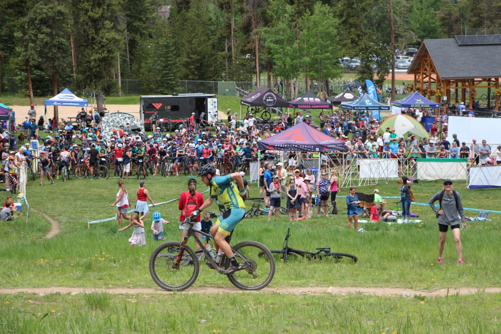 A mountain biker pedals past crowds at the Firecracker 50 mountain bike event at Carter Park in Breckenridge on Thursday.