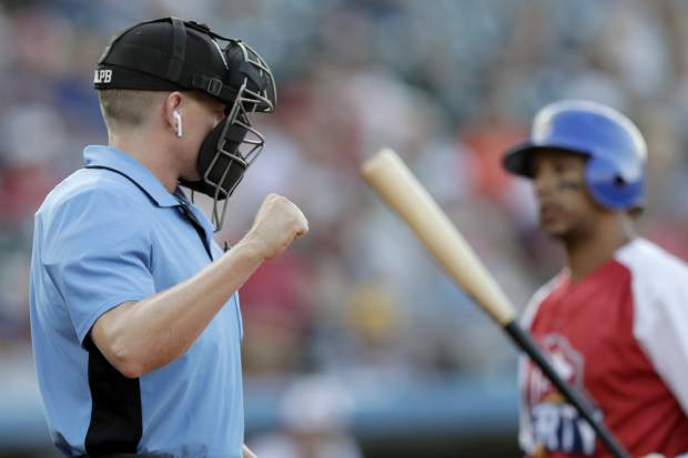 Home plate umpire Brian deBrauwere, left, calls a strike given to him by a radar system over an earpiece as Liberty Division's Tyler Ladendorf, right, of the High Point Rockers, strikes out to Freedom Division's Mitch Atkins, of the York Revolution, during the first inning of the Atlantic League All-Star minor league baseball game on Wednesday in York, Pennsylvania.