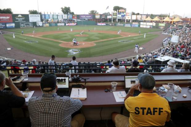 Ron Besaw, right, operates a laptop computer as home plate umpire Brian deBrauwere, gets signals from radar with the ball and strikes calls during the fourth inning of the Atlantic League All-Star minor league baseball game on Wednesday in York, Pennsylvania.