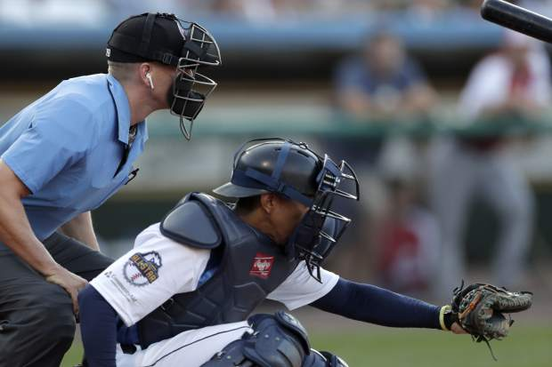 Home plate umpire Brian deBrauwere, left, huddles behind Freedom Division catcher James Skelton, of the York Revolution, as the official wears an earpiece during the first inning of the Atlantic League All-Star minor league baseball game on Wednesday in York, Pennsylvania,