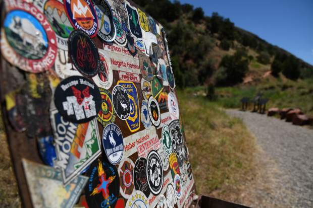 The guest book container is covered with fire agency stickers from across the western United State at the trail head of the Storm King trail. Saturday, July 6 is the 25 year anniversary of the South Canyon fire which took the lives of 14 wildland firefighters.