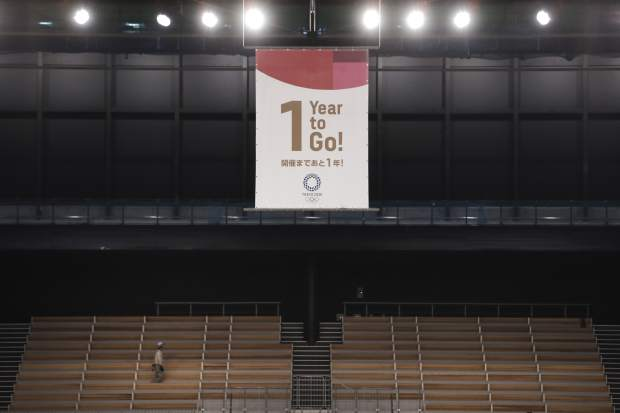 A worker walk near a 1 Year to Go banner at the Ariake Gymnastics Center, Monday, July 22, 2019, in Tokyo. Despite scandals, rising costs and doubts about the economic payoff, the Tokyo Olympics will be a must-see event — if you can find a ticket or a hotel room — when they open in a year. Tokyo was supposed to be a
