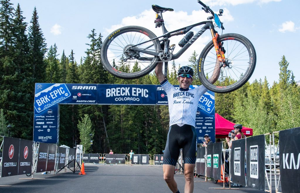 Jeremiah Bishop hoists his bike in the air in Breckenridge after crossing the finish line to win the 2018 Breck Epic.