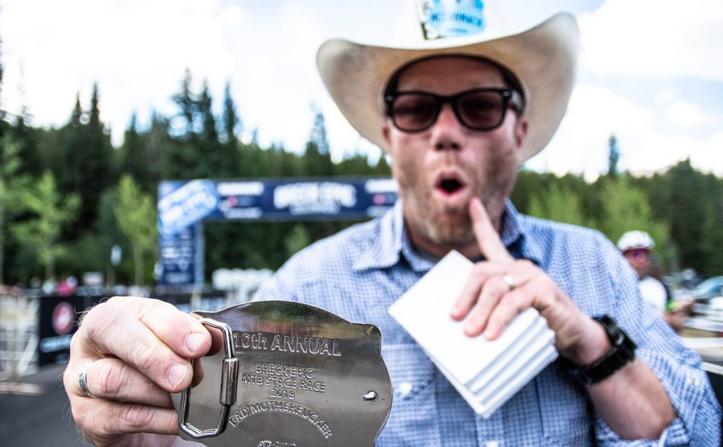 At the finish line in Breckenridge last August, Breck Epic founder and race director Mike McCormack shows off the belt buckle awarded to mountain bikers who are able to finish the six-day, multistage mountain bike race.