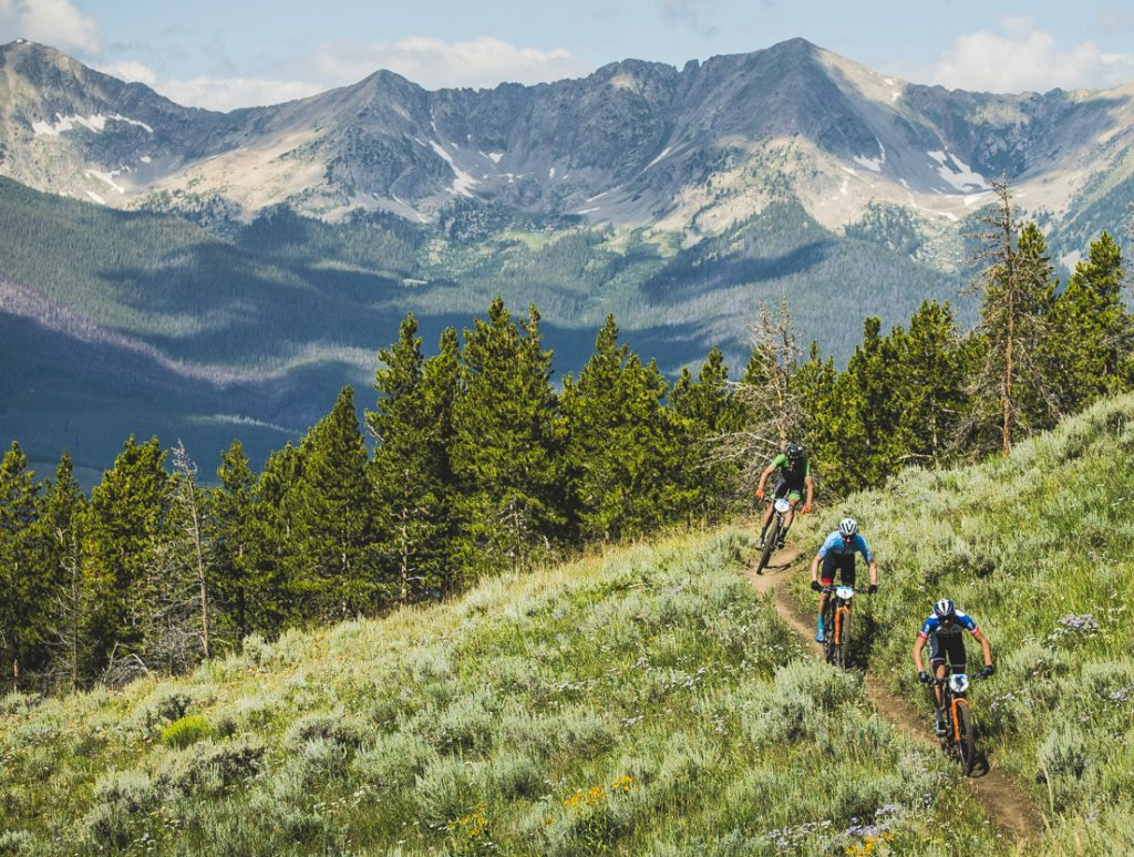 Lead mountain bikers pedal singletrack during Monday morning's second stage of the Breck Epic, the Tenmile Range in view in the background.