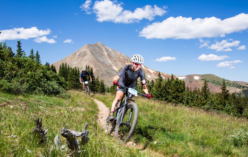 Echo Rowe (front) and Dean Cahow ride singletrack, with Mount Guyot in view in the background, during Tuesday's third stage of the 6-day Breck Epic mountain bike race.