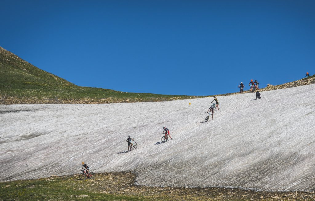 Mountain bikers negotiate their way through a lingering snowfield on the above-tree line slopes of Mount Guyot during Tuesday's third stage of the 2019 Breck Epic multi-stage 6-day mountain bike race.