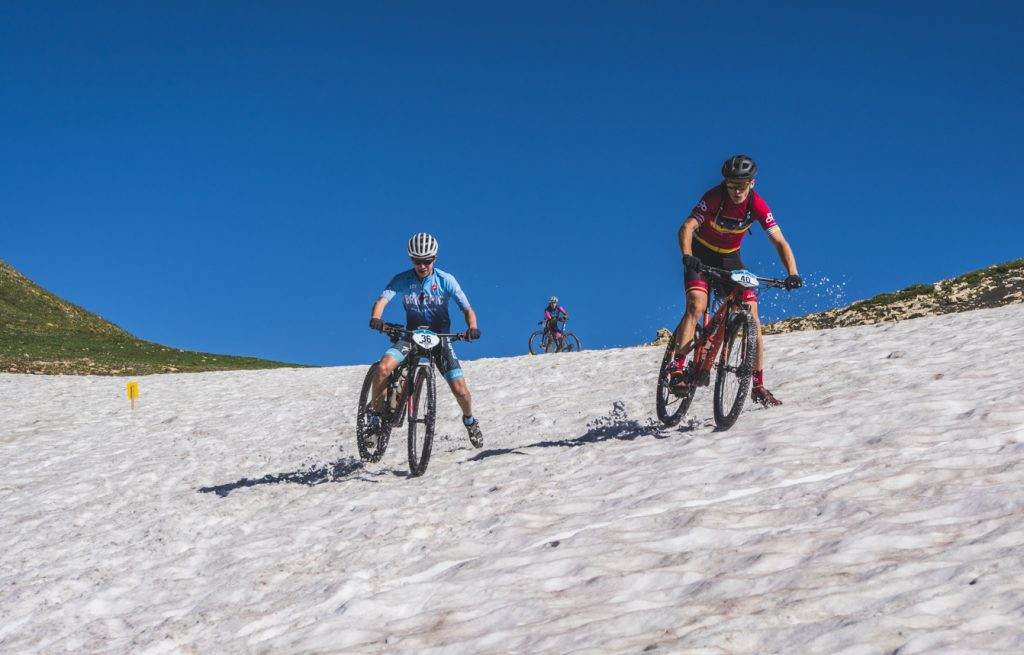 Mountain bikers Juan Cordova (left) and Carter Nieuwesteeg manage their way through a lingering snowfield on the above-tree line slopes of Mount Guyot during Tuesday's third stage of the 6-day Breck Epic mountain bike race.