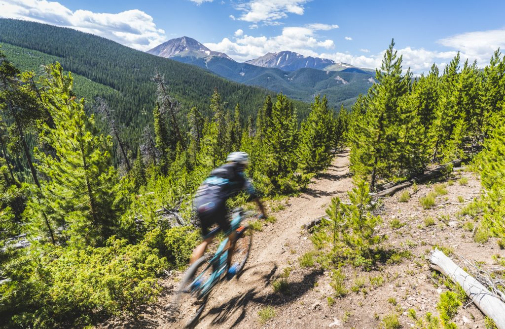 A mountain biker rides during the fourth stage of this year's six-day Breck Epic mountain bike race, the 41-mile Aqueduct, Mounts Guyot and Baldy in view in the background.