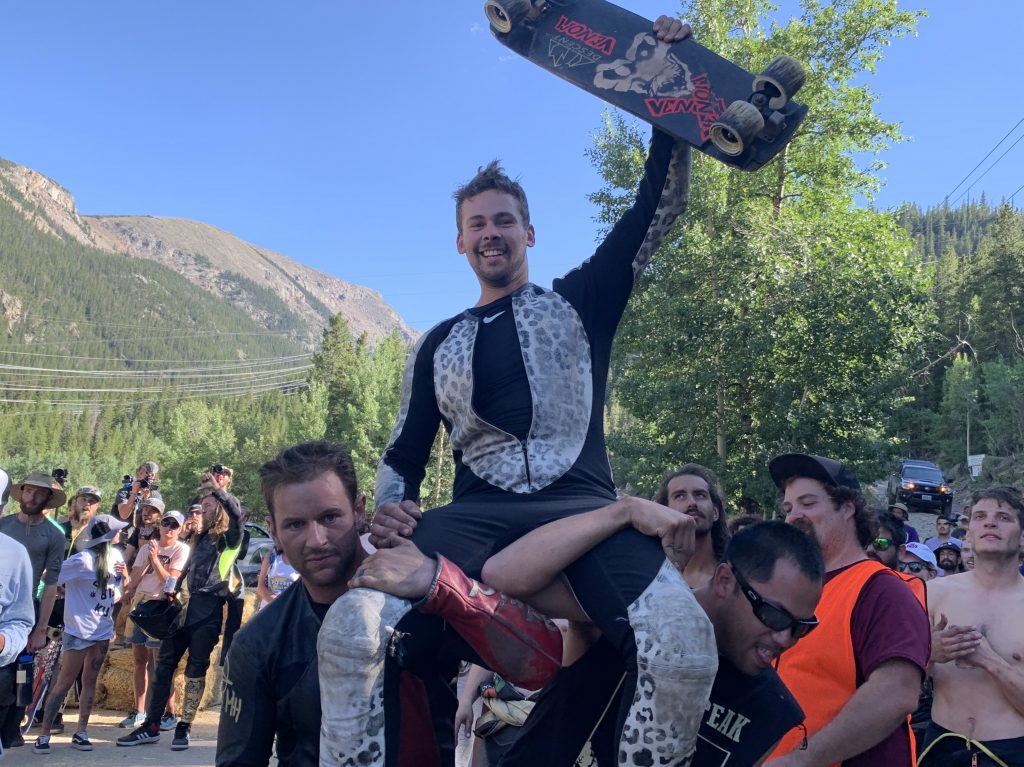 Boulder resident Daina Banks, raised in Dillon Valley, hoists his skateboard in the air while friends carry him up to the hay bale podium after his runner-up finish at Sunday's Devil's Peak Downhill skateboard race at Guanella Pass in Georgetown.