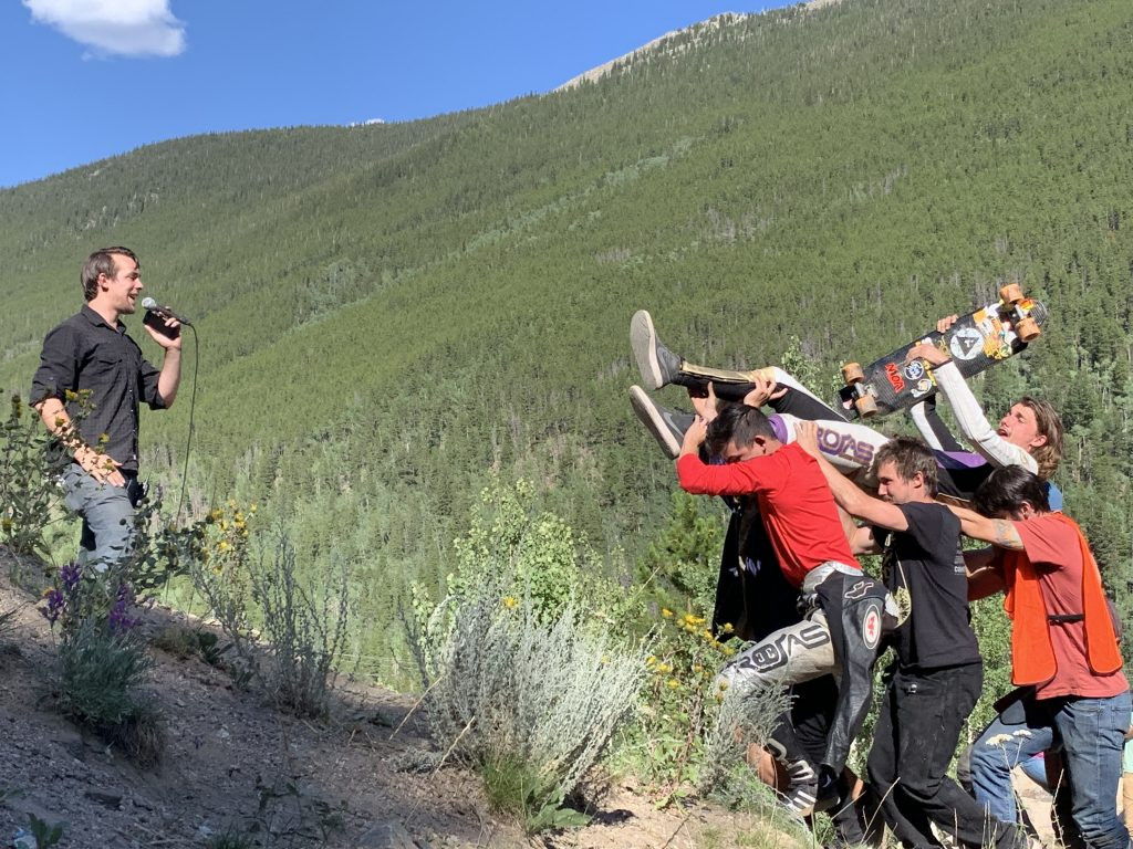 Friends and fans carry Chase Hiller of Branson, Missouri up to the hay bale podium and race director Justin Rolo emcees after Hiller's win at Sunday's Devil's Peak Downhill skateboard race at Guanella Pass in Georgetown.