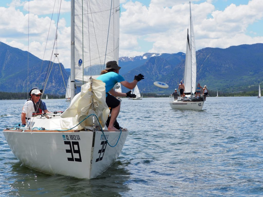 A sailor attempts to catch a frisbee thrown from skipper Josh, Bowens-Rubin'sJ-24 boat dubbed Zero Gravity (at right) during this weekend's 2019 Dillon Open on Lake Dillon.