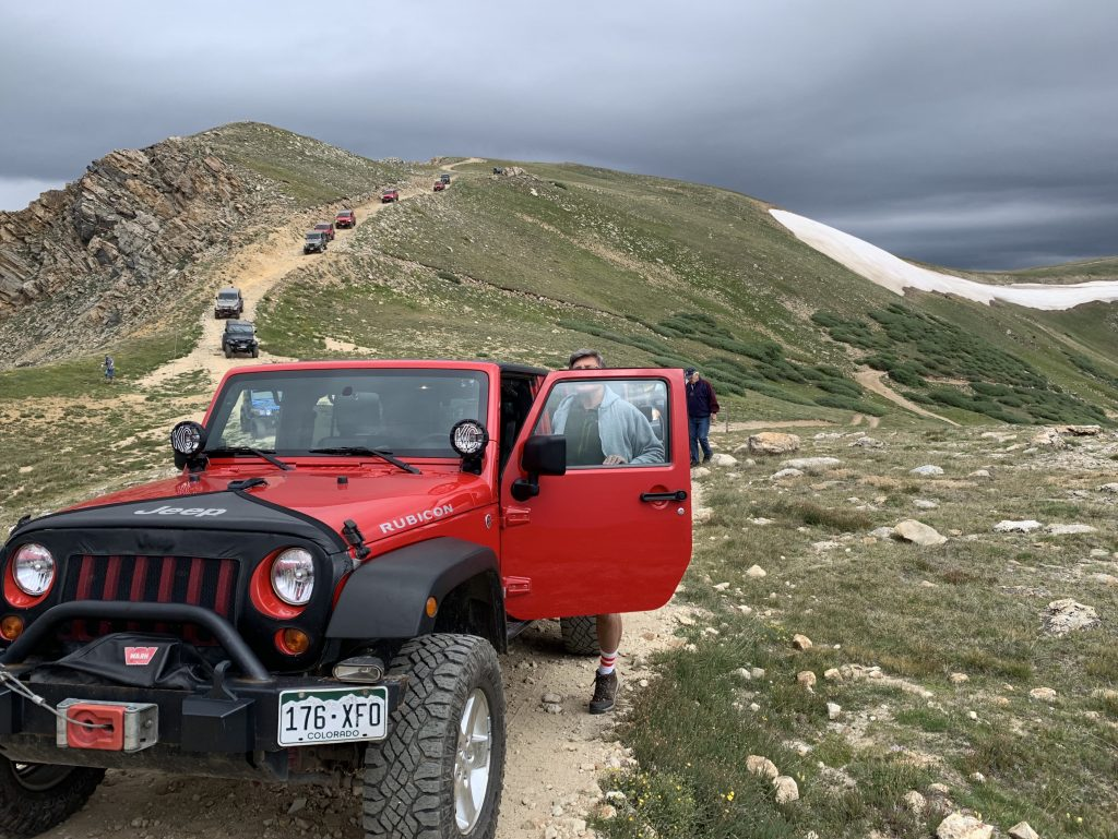 A parade of Jeeps descend a steep hill while riding the Saints John Jeep road on Aug. 10.