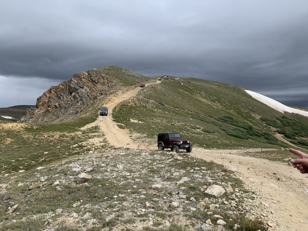 A parade of Jeeps descend a steep hill while riding the Saints John Jeep road on Aug. 10, 2019.