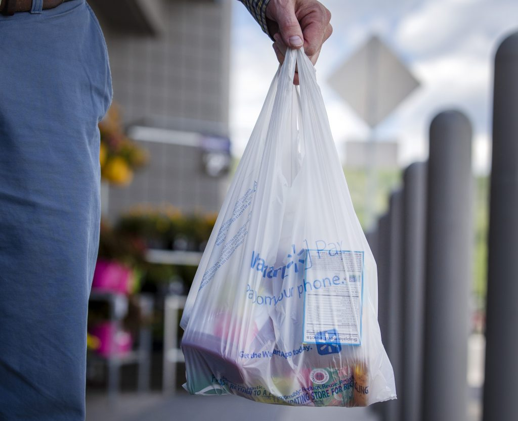 Plastic bag in hand, a customer leaves a store in Frisco, Colo. on Wednesday, Aug. 14, 2019.