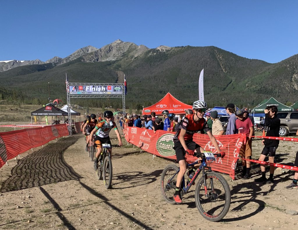 Lasse Konecny, second from right, refuels after crossing the finish line before another lap during Sunday's first meet of the 2019 Colorado High School Cycling League mountain bike season, the Frisco Bay Invitational at the Frisco Peninsula.