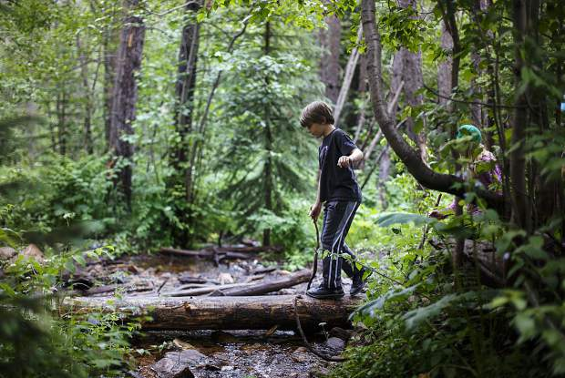 Ollie Dautremont, 8, of Iowa, carefully crosses a stream while hiking the Lily Pad Lake Trail while hiking with his family July 12 in Silverthorne.