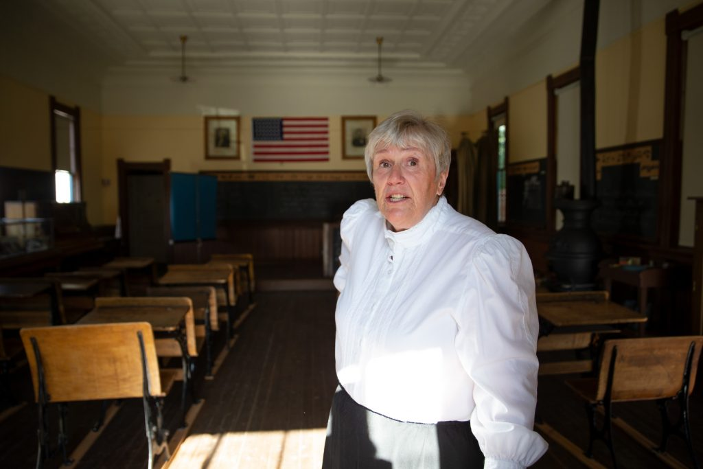 "In traditional dress, Christy Nelson, local historian and ""school-marm"" rings the bell at Dillon's historic 1883 School House on Thursday, Aug. 22, and speaks about the history of the building."