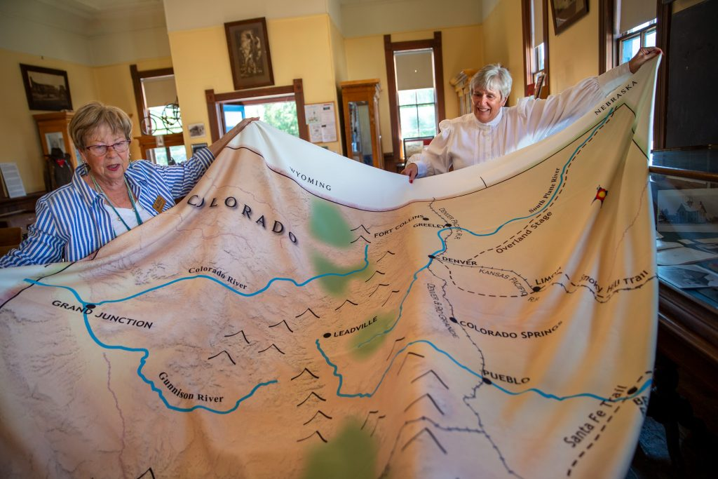 Sally Queen, left, and Christy Nelson hold up a giant fabric map of the state of Colorado in the one-room 1883 Dillon Schoolhouse on Thursday, Aug. 22, 2019.