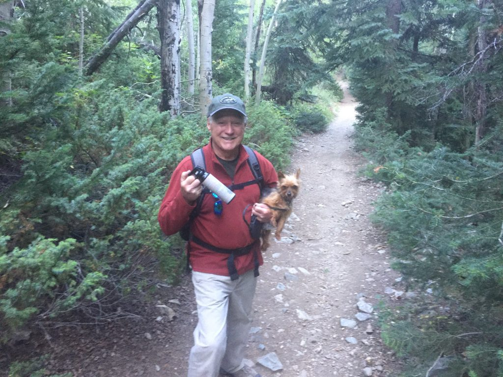 Michael Rohr stands on the trail with his dog, Razzle Dazzle, and a can of bear spray following an encounter with a moose.