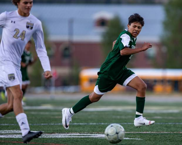 Alan Casillas (16) and Harrison Rubis (24) sprint for the ball during the first half of the Summit boys varsity soccer team's home game versus Battle Mountain at Summit High in Breckenridge on Sept. 17.