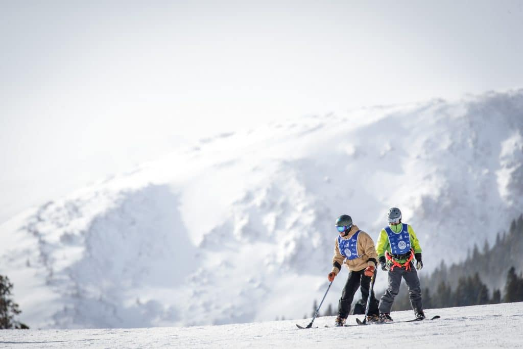 A pair of adaptive skiers on the slopes.