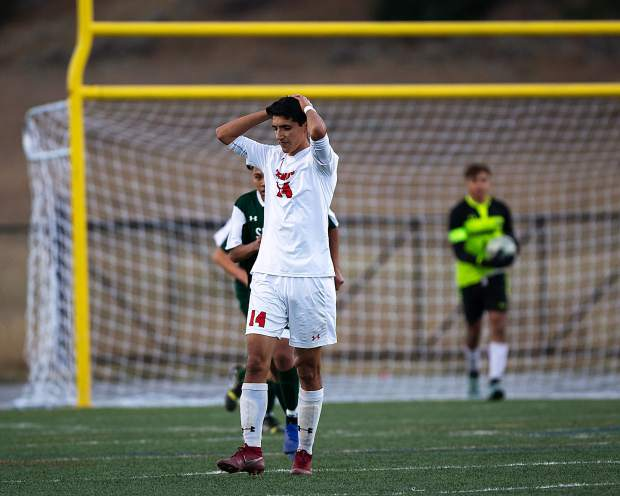 Glenwood Springs' Angel Bernal (14) reacts after Summit High goalkeeper Chris Lopez (background) saved his shot during the first half of Summit's 1-0 upset win over Glenwood Thursday night at Tiger Stadium in Breckenridge.