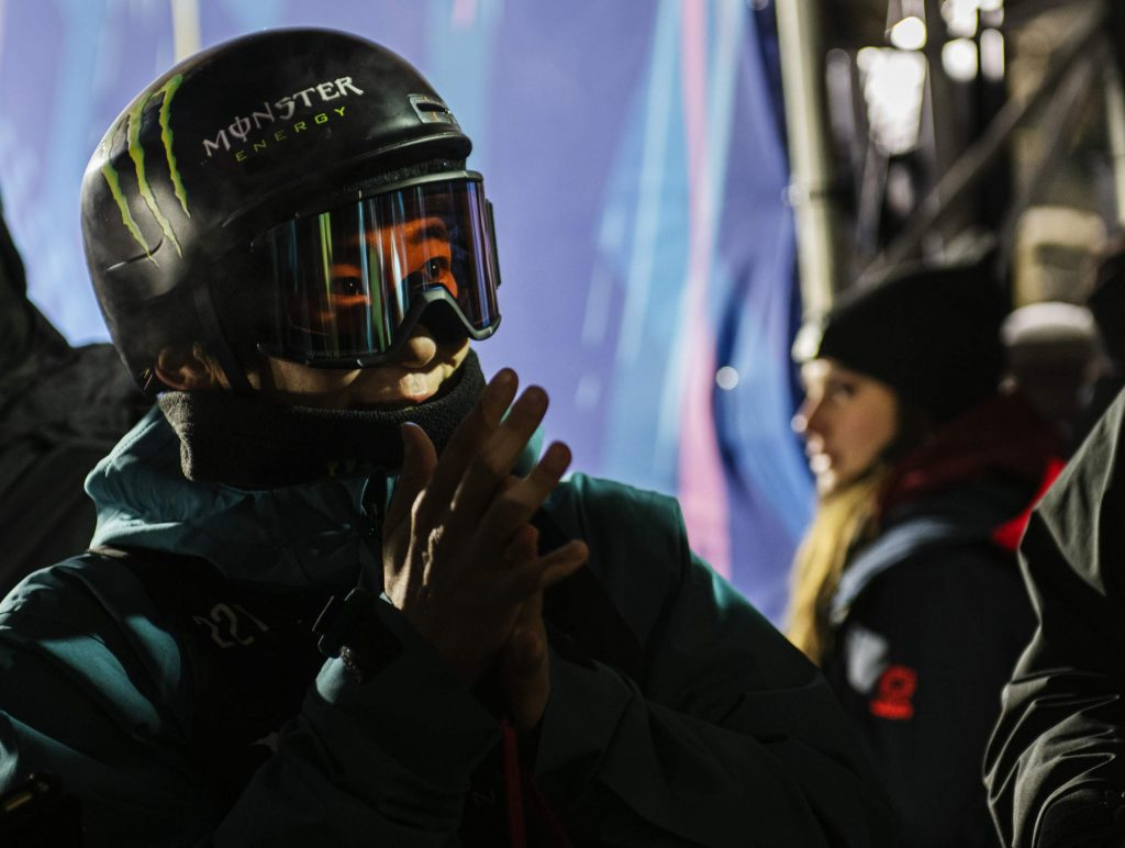 Yuto Totsuka watches his competitors on a television at the top of the superpipe during the X Games Men's Snowboard Superpipe Final on Thursday, Jan. 23, 2020.