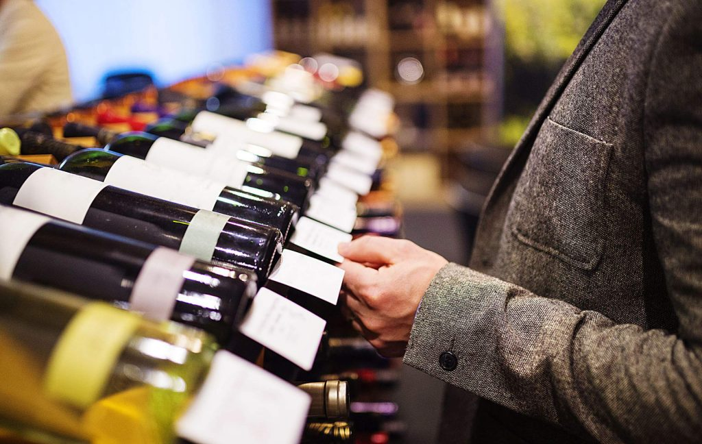 Unrecognizable young man in a wine shop choosing a wine